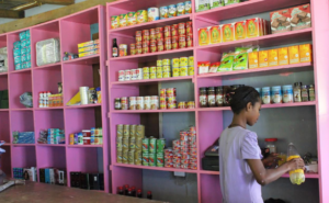 A young girl organizes canned goods at her family's store